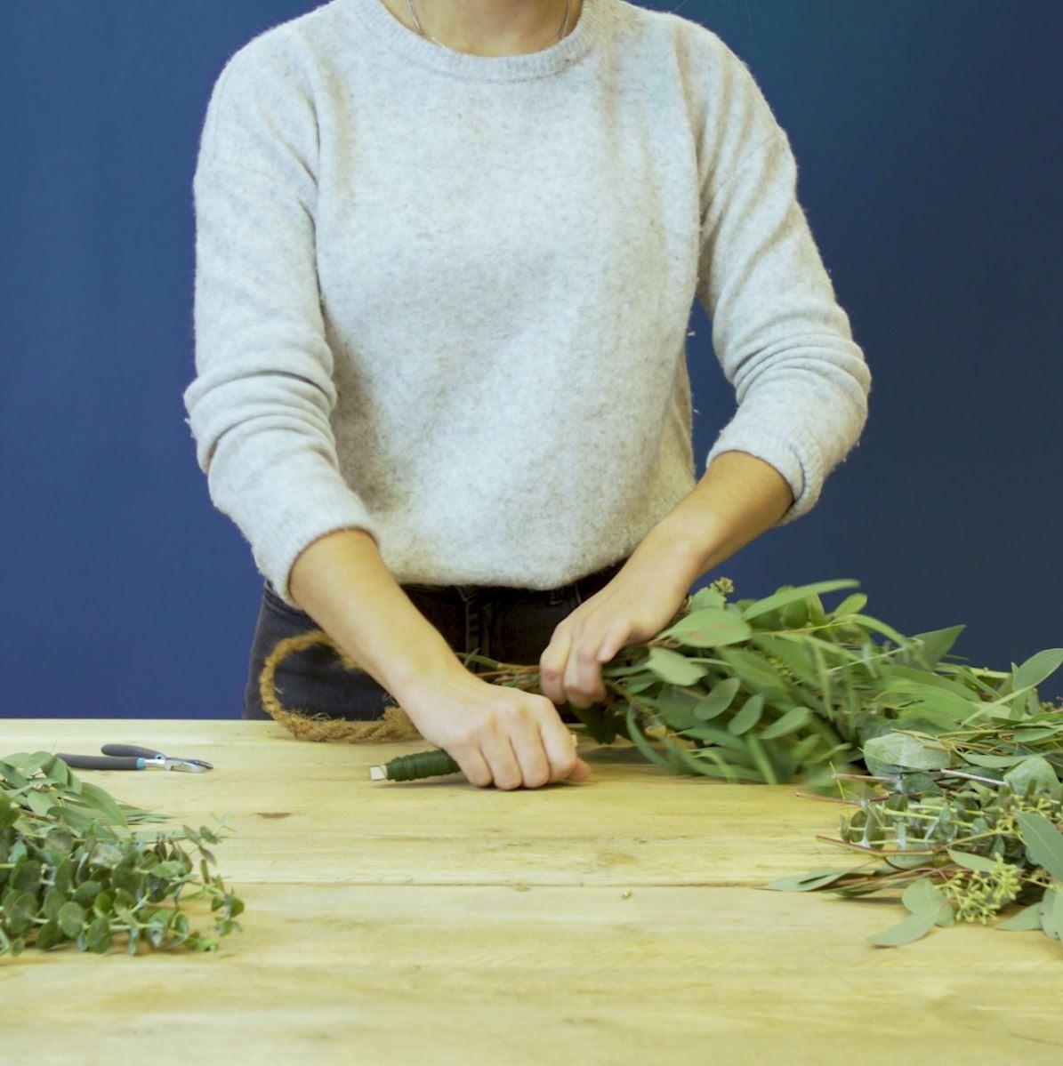 DIY groene tafelloper. Stap 3: Bind de takken aan het touw